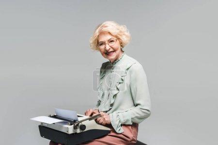 Photo pour Heureux senior femme en utilisant machine à écrire sur gris - image libre de droit