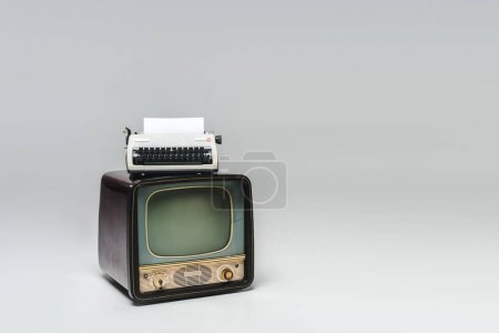 vintage tv with typewriter on top on grey surface