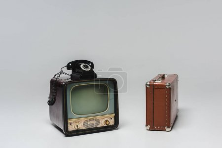 vintage tv with rotary phone and suitcase on grey