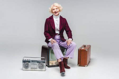 attractive senior woman sitting on vintage tv on grey