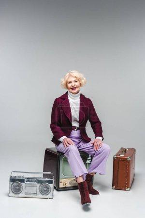 happy senior woman sitting on vintage tv on grey