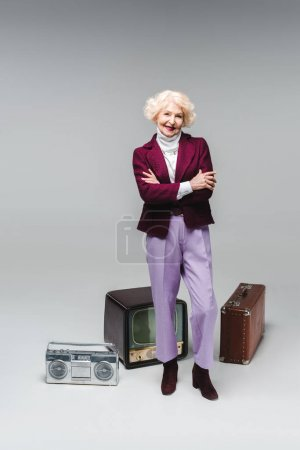 beautiful senior woman with crossed arms standing in front of vintage tv, boombox and suitcase on grey
