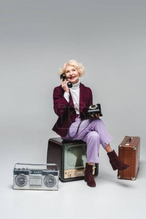 beautiful senior woman talking by phone while sitting on vintage tv on grey