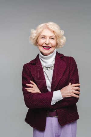 smiling senior woman with crossed arms isolated on grey
