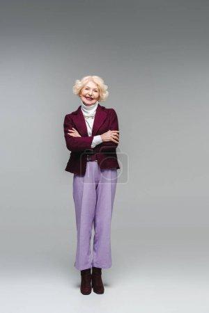 Photo pour Femme âgée souriante avec les bras croisés dans des vêtements élégants regardant la caméra sur gris - image libre de droit