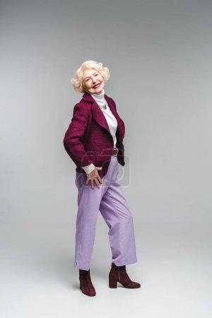 Photo pour Belle femme senior dans des vêtements élégants, regardant la caméra sur fond gris - image libre de droit