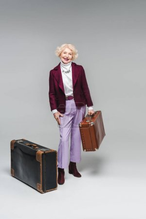 smiling senior woman with vintage suitcases on grey