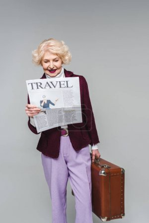beautiful senior woman holding suitcase and reading travel newspaper isolated on grey