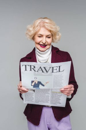 beautiful senior woman reading travel newspaper isolated on grey