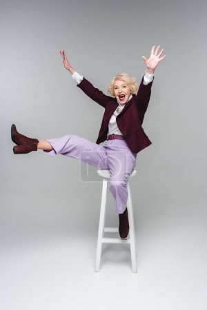 screaming funny senior woman sitting on chair with raised hands and leg on grey