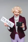 beautiful senior woman with travel newspaper and film camera isolated on grey