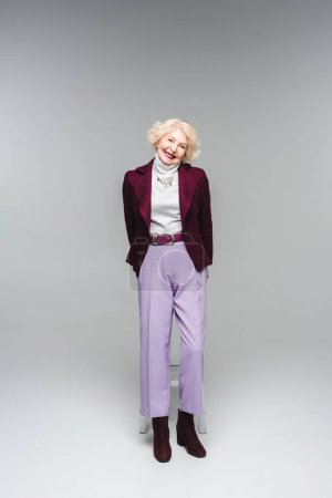 beautiful senior woman in stylish vintage clothes on grey