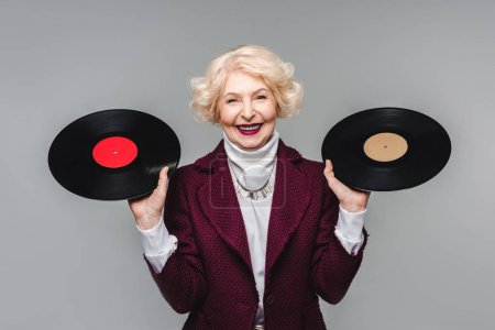 happy stylish senior woman holding vinyl discs isolated on gray background