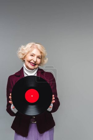 smiling stylish senior woman holding vinyl disc isolated on gray background