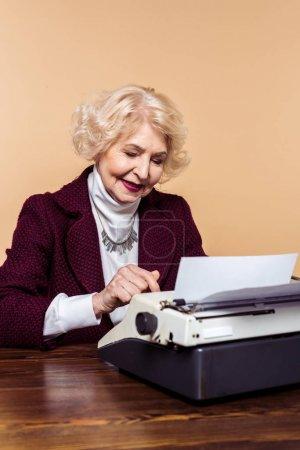 fashionable senior woman using typewriter at table