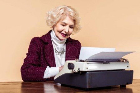 stylish senior woman using typewriter at table