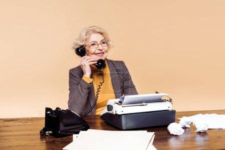fashionable stylish senior woman in eyeglasses talking on rotary phone at table