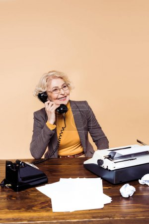 smiling stylish senior woman in eyeglasses talking on rotary phone at table