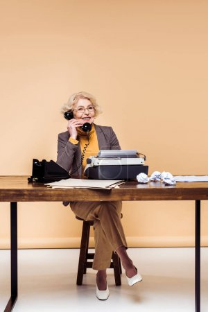 smiling stylish senior woman talking on rotary phone at table