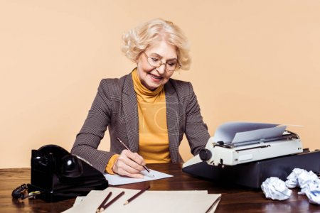 stylish senior woman writing on paper at table with typewriter and rotary phone
