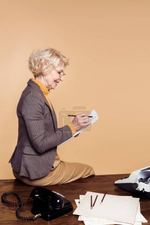 side view of stylish senior woman writing on paper and sitting on table with typewriter and rotary phone