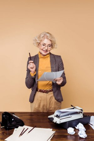 stylish senior woman in eyeglasses looking at paper near table with typewriter and rotary phone