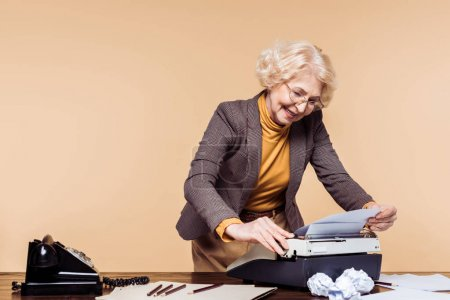 smiling senior woman using typewriter at table with rotary phone