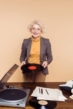 stylish senior woman holding vinyl disc near table with record player