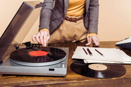 cropped image of woman turning on vinyl record player