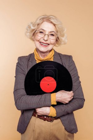 happy stylish senior woman holding vinyl disc isolated on beige background