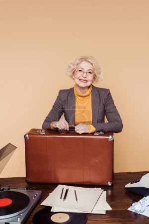happy stylish senior woman with vintage suitcase at table with vinyl disc, record player and typewriter