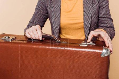 cropped shot of stylish woman closing vintage suitcase isolated on beige background