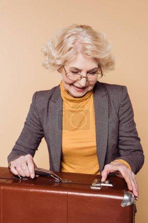 fashionable senior woman in eyeglasses closing vintage suitcase isolated on beige background