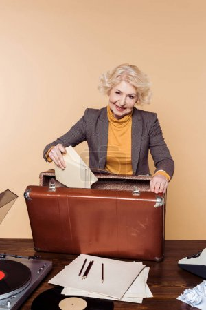stylish senior woman putting books in vintage suitcase on table with record player and vinyl disc