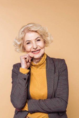 fashionable senior woman posing isolated on beige background