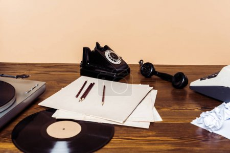 rotary phone, vinyl disc, record player and typewriter on wooden table