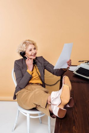 stylish senior woman with legs on table talking on rotary phone and looking at paper