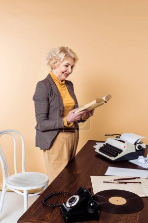 smiling senior woman reading book near table with rotary phone, vinyl disc and typewriter