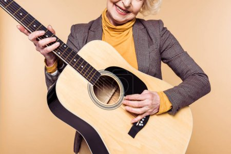 Photo for Cropped image of stylish woman playing on acoustic guitar isolated on beige background - Royalty Free Image