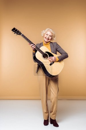 smiling stylish senior woman playing on acoustic guitar