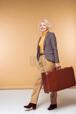 stylish senior female traveler holding vintage suitcase
