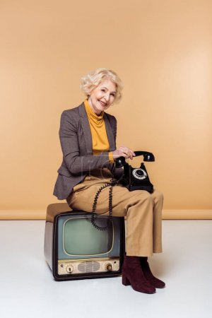smiling stylish senior woman with rotary phone sitting on vintage tv