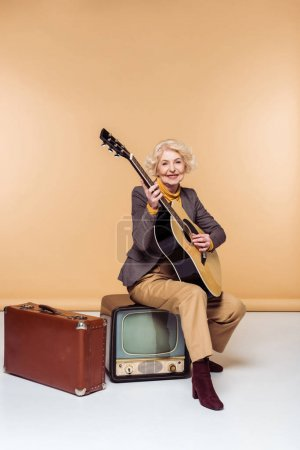 senior woman with acoustic guitar sitting on vintage tv near old suitcase