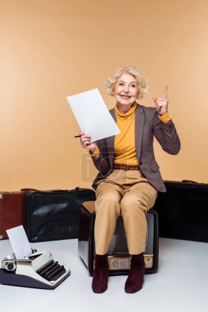 Photo for Smiling stylish senior woman with finger raised holding paper and sitting on vintage tv near typewriter and suitcases - Royalty Free Image