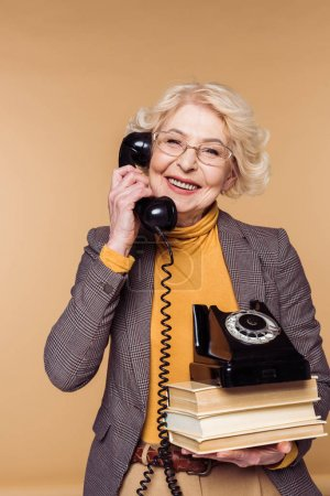 happy fashionable senior woman in eyeglasses talking on rotary phone and holding stack of books