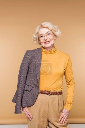 happy fashionable senior woman in eyeglasses holding jacket on shoulder
