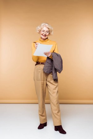 stylish senior woman in eyeglasses holding jacket and writing on paper