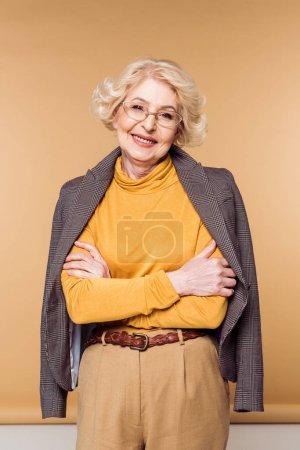 happy stylish senior woman in eyeglasses posing with jacket on shoulders