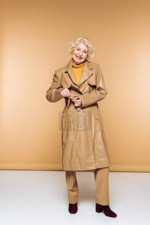 Photo pour La mode femme senior attacher la ceinture de trench-coat en cuir - image libre de droit