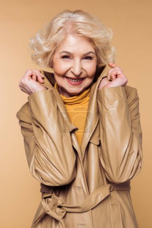 smiling stylish senior woman posing and holding collar of trench coat